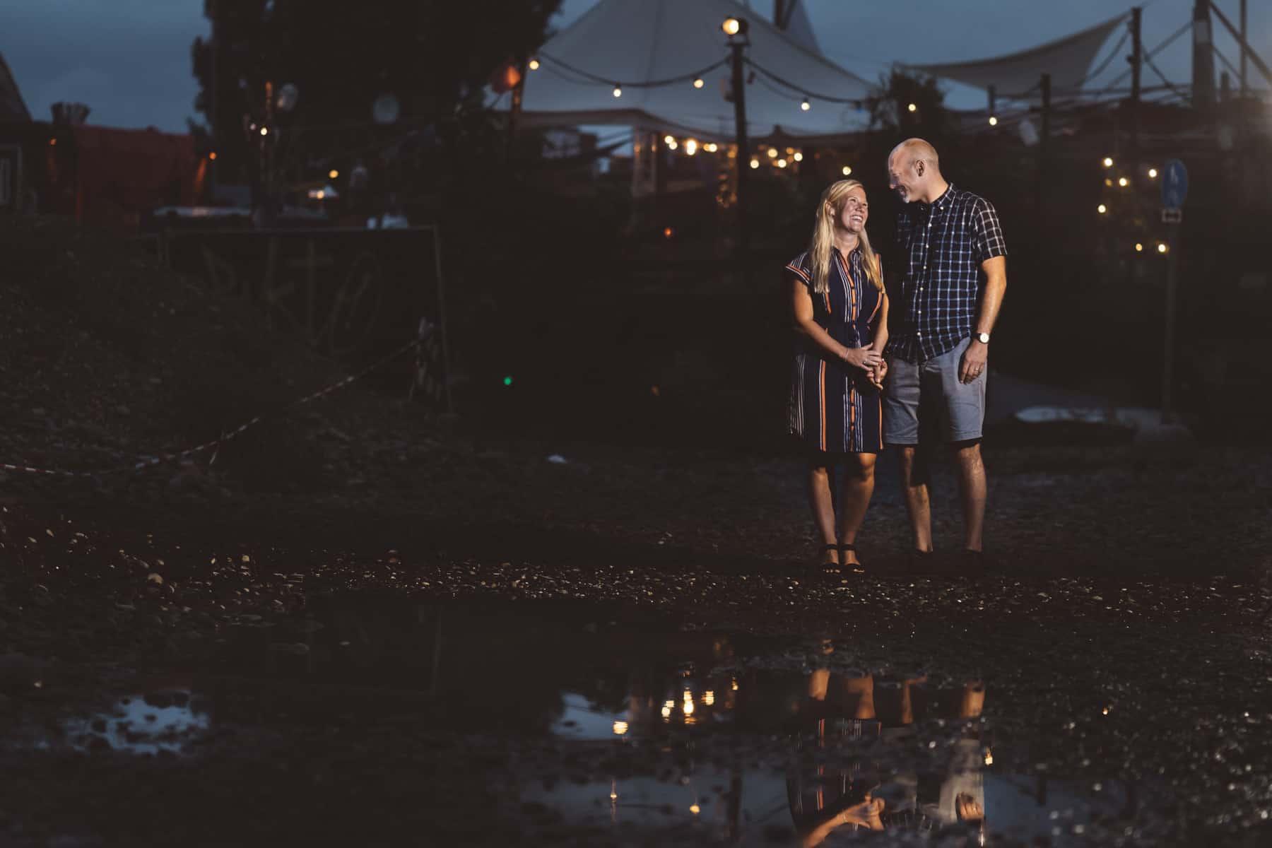 Paar vor Lichtern mit Spiegelung in Pfütze